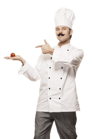 toque blanche: Chef with beard pointing at a tomato that lies in his hand, isolated on white