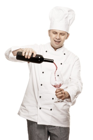 toque blanche: Chef pouring red wine into a glass, isolated on white