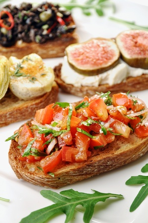 Different bruschetta toppings, tomato+onions+balsamico+basil; artichoke+goat cheese; ricotta+fig,olives+capers+chillies+parsley