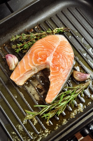 Salmon steak being fried in a pan with rosemary,thyme and garlic photo