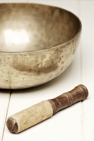 music therapy: singing bowl on a white table, selective focus Stock Photo