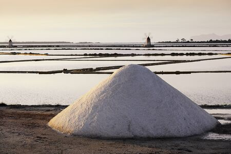 trapani: Heap of Salt infront of sicilian salt mills in Trapani in late low standing evening light Stock Photo