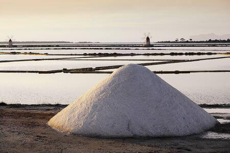 Heap of Salt infront of sicilian salt mills in Trapani in late low standing evening light Standard-Bild