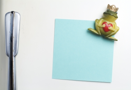 Blank note on fifties fridge-door, close-up of frog with crown holding a heart magnet  photo