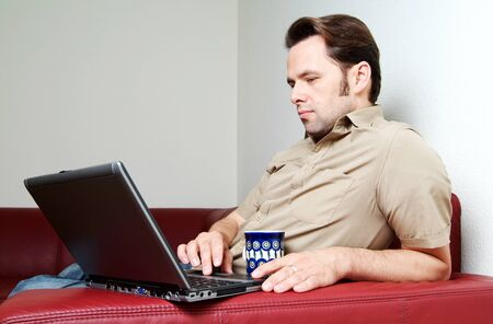 red sofa: Man doing some laptop worh at home, sitting on  red sofa