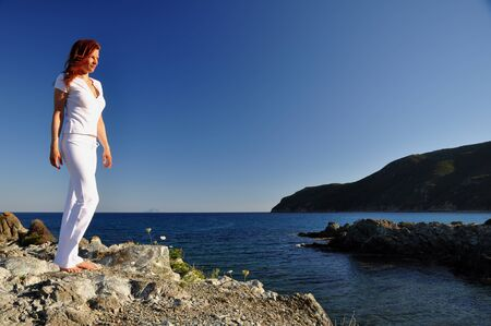 traquil scene: Redheaded woman standing on a rock at the sea and gazing at the late evening sun