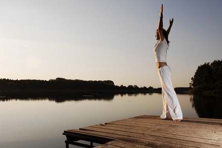Woman Doing Yoga At A Lake In Nice Morning Light