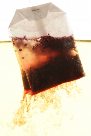 changing color: Rosehip - hibiscus Tea bag hanging into hot water, tea descending into water and changing color Stock Photo