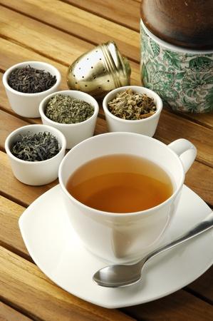 Kopje thee met verschillende soorten thee bladeren in kommen