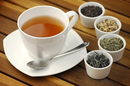 Cup of tea with different sorts of tea leaves in bowls