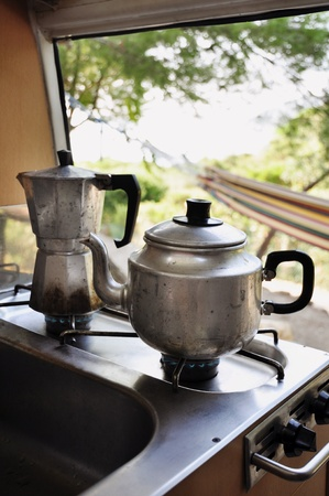 Cooking tea and coffee pot in camping surrounding, view from camping van towards hammock outside photo