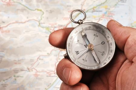 Hand bedrijf kompas, kaart (van de focus) op de achtergrond. OPMERKING: het is een oud kompas dat wat stof en vuil achter het glas bevat Stockfoto