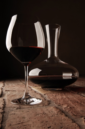 Red wine in decanter on rustic stone floor