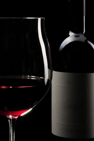 Red wine glass and bottle infront of black background photo