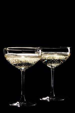 Two coupe glasses of sparkling champagne infront of black background