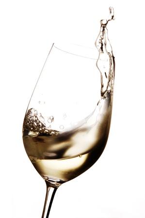 Witte wijn wordt gezwenkt in een glas, het glas is een beetje beslagen, omdat de wijn gekoeld Stockfoto