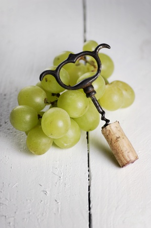 Cork screw and white grapes Stock Photo
