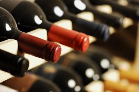 alcohol bottle: Wine bottles stored in a shelf, very shallof DoF