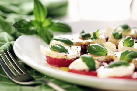 Fresh caprese salad with delicious tomatoes + mozzarella and basil; selective focus