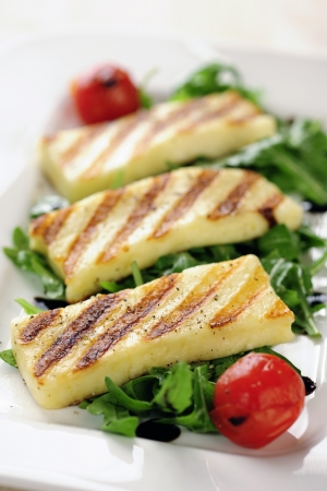 Grilled Halloumi cheese on rocket salad Stock Photo