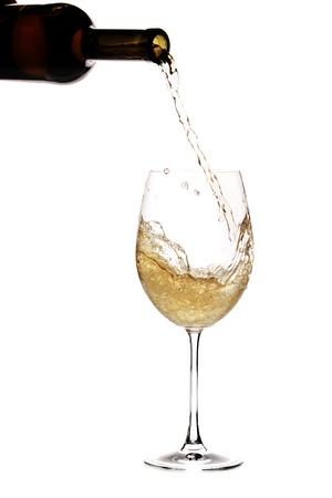 Witte wijn wordt pourred in een glas uit een fles
