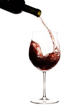 Rode wijn wordt pourred in een glas uit een fles wijn