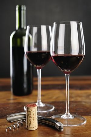 Twee glazen rode wijn; kurk met Barolo Italia en kurkentrekker; selectieve aandacht Stockfoto
