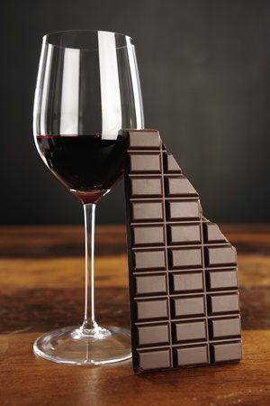 Glass of red wine and chocolate bar, selective focus