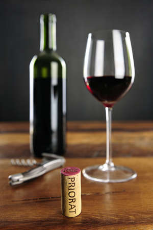 Priorat Cork - which is one of the best spanish vine planting areas, glass of red wine, bottle and corkscrew, focus on cork photo