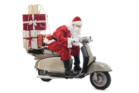Santa Claus on vintage scooter with stack of christmas presents, isolated on white Standard-Bild