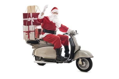 Santa Claus on vintage scooter with stack of christmas presents, isolated on white Stock Photo
