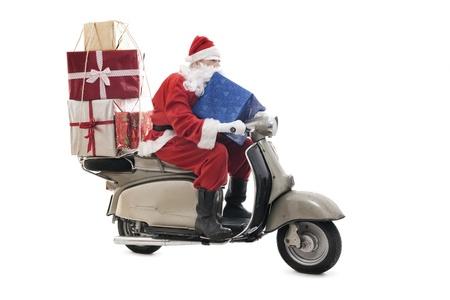 Weihnachtsmann auf Vintage Roller mit Stapel von Weihnachtsgeschenke, isoliert auf weiß Standard-Bild - 21956513