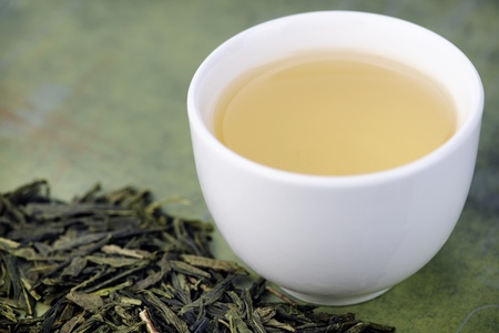 Loose green tea and cup, selective focus on tea leaves