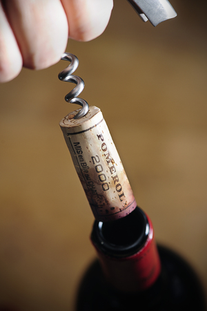 Opening a wine bottle Pomerol 2000, Hand pulling a cork on a corkscrew off the bottle, Pomerol is the famous vine planting area in France for Bordeaux wine, selective focus
