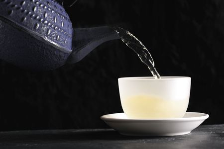 Teapot poring green tea into a cup, infront of black background, shallow DoF
