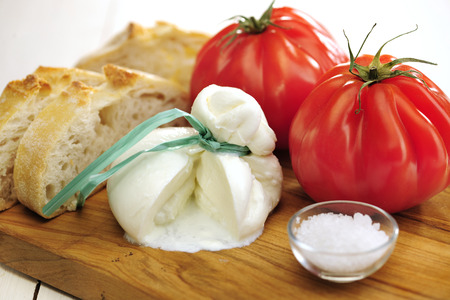 Burrata (sort of very fresh mozzarella cheese), tomato and bread, selective focus Stock Photo