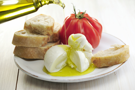 Burrata (sort of very fresh mozzarella cheese), tomato and bread, olive oil being poured on cheese, selective focus