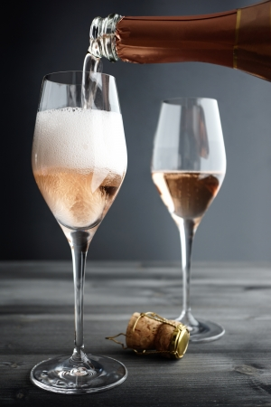 Rose Champagne / Pink Champagne being filled into Glass, selective focus