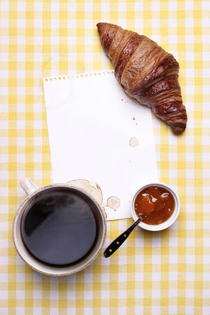 Breakfast scene with Coffee, Croissant, Jam and Blank Paper with Copyspace  photo