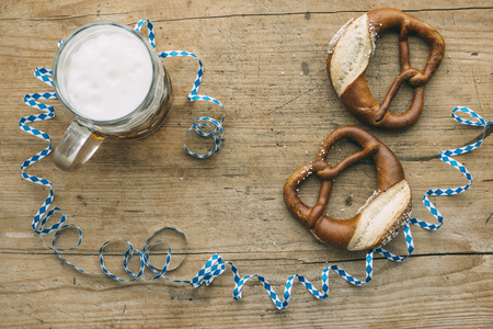 Oktoberfest: Masskrug of beer, Pretzels and bavarian streamer on rustic wooden table Stock Photo