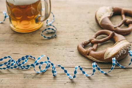Oktoberfest: Masskrug of beer, Pretzels and bavarian streamer on rustic wooden table Stock Photo