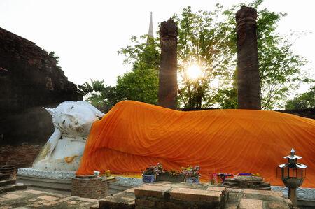 peaking: Sleeping Buddha in Wat Yai Chaimongkhon, Ayutthaya; sun peaking through the leaves