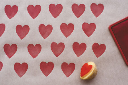 DIY wrapping paper decorated with heart shaped potato stamp