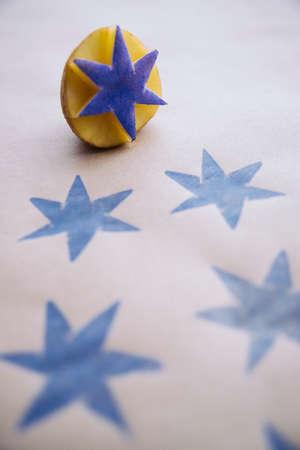 DiY inpakpapier met blauwe sterren bedrukt met een gesneden aardappel stempel