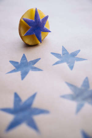 DiY wrapping paper with blue stars printed with a carved potato stamp