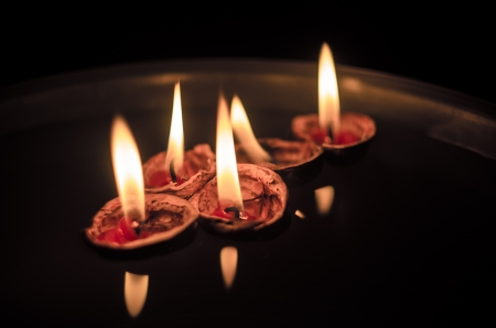 transport interior: Walnut Shells with Lit up Candles Floating in a Bowl of Water Stock Photo
