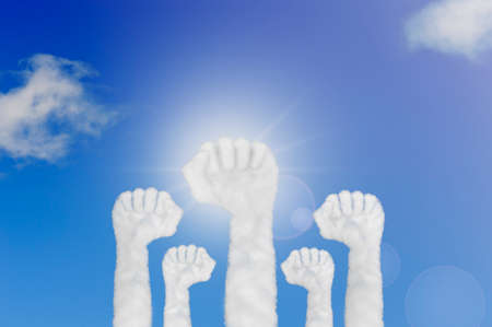 Cloud shape of hands raised fist air on blue sky. Concept labor movement or corporate celebration.