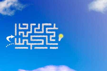 Cloud shape of labyrinth or maze start and finish with a light bulb on blue sky. Idea or success, creative and innovation business concept