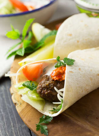 Middle eastern lamb kofta wraps with tomato and yoghurt served on a dark wooden plate