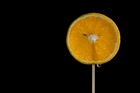 lolli: round orange slice on a stick, black background for your text Stock Photo